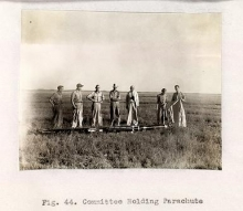 "black and white photo of 7 men standing in a field captioned ""Fig. 44. Committee Holding Parachute"""