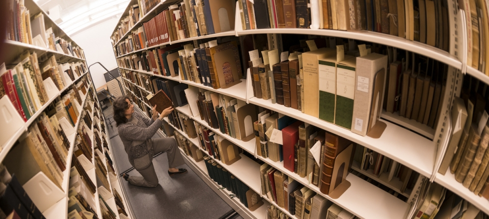librarian kneels between two long shelves of books as she places one back on the shelf