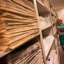 Woman browsing and reading newspaper stacks