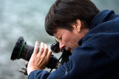 A bearded man in profile, wearing a hoodie, looks into the viewfinder of a large camera that is pointed slightly upwards at an angle.