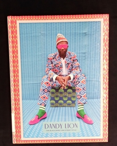 Cover of the book Dandy Lion showing a man in a vivid abstract suit sitting on a box covered in a checkerboard pattern