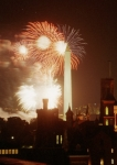 Fireworks illuminate the Washington Monument in Washington DC. In the foreground is the silhouette of the Smithsonian Castle.