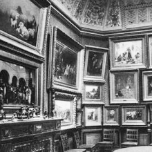 photo of interior walls hung with many paintings