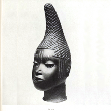 Bronze portrait bust of a person with a textured conical hat, from Benin.