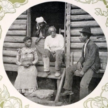 Photo of several people sitting outside a log cabin.