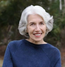 Headshot of a woman, smiling, with short, wavy white hair. She wears a blue sweater and there are trees in the background.