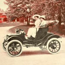 two women in an open top electric car from 1915