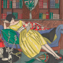 Woman lounging on a couch in a private library reading a book.