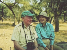 A older man and an older woman sit in the African savannah. The man has binoculars on his head and both are wearing hats and loose clothing.