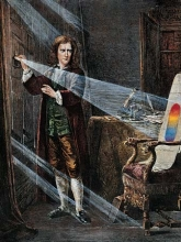 A colored engraving of Sir Isacc Newton, dressed in typical late 1800's clothes, stands by a window whose shutters are closed. He holds a prism in the light from a hole that is projected across the room to appear as a rainbow on the back of a chair.