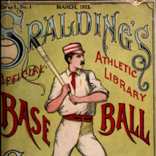Early 20th century mustachioed baseball player holding a bat with the word Spalding above his head.