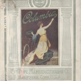 "Cover of Columbia bicycle catalog, 1912, showing a woman kneeling painting the words ""Columbia"" while crowning a bicycle with a laurel wreath."