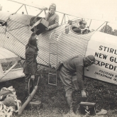 photo of men in old fashioned flying gear sitting in and loading a two-person prop plane
