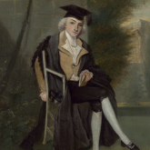 Painting of a young man in late 1700's attire wearing a graduation cap and gown, sitting outdoors in a chair, holding a book