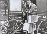 BW photo of post man half sitting in US Mail cart