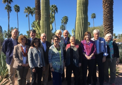 A small group of people stand before some very large cactuses and palm tree