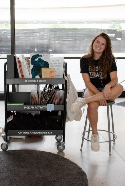 Chaptour Guide sits by the Check it Out cart